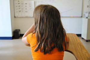 Mädchen einsam auf der Schulbank