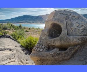 Totenkopf aus Stein am Wasser